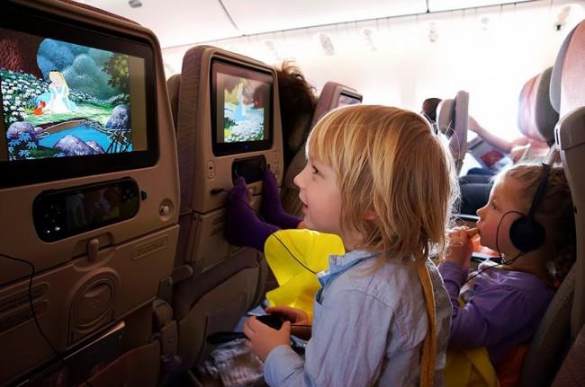 Детей стараются развлечь в самолете, чтобы перелет не был слишком утомительным. Малыши с удовольствием смотрят мультфильмы.